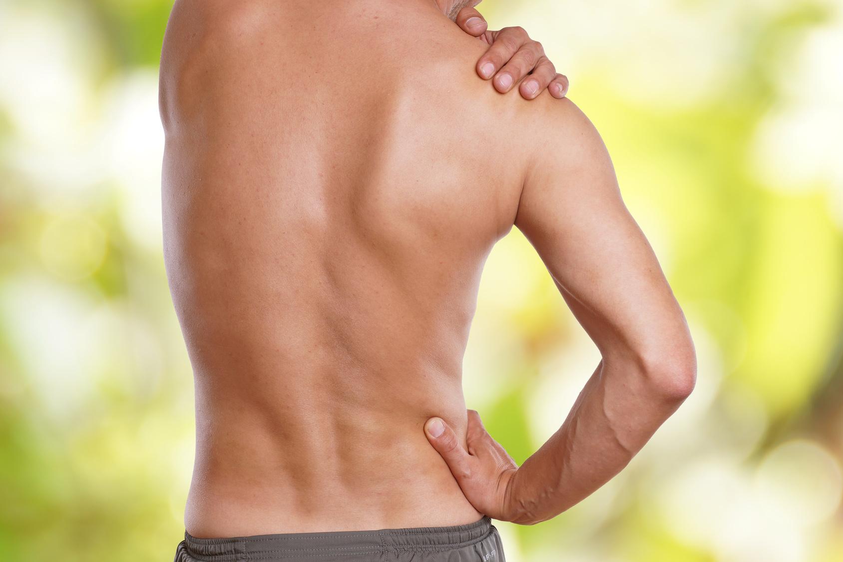 Mann hat Schmerzen im Rücken vor grünen Hintergrund